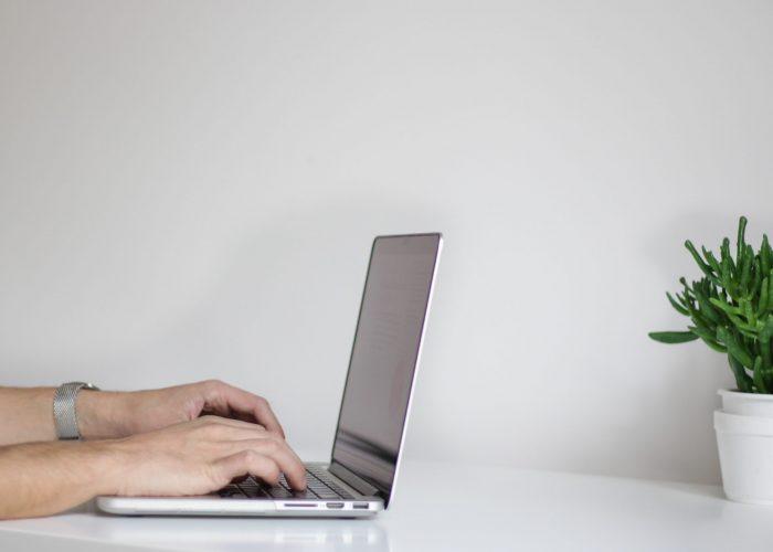 A perosn at a desk using a laptop